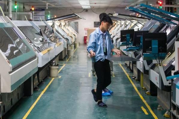 东莞五株科技的手机hdi电路板生产车间,操作机器的技工给机器加料